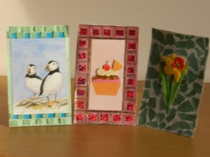 The picture on the left and in the centre have been framed with mosaic and the flower picture on the right has an abstract design from torn, green paper that gives it a soft look.